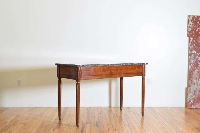 Having a shaped thick marble top with rounded front corners and notched rear corners, the frame having fluted corners and round tapering fluted legs, the panel with rectangular carvings.