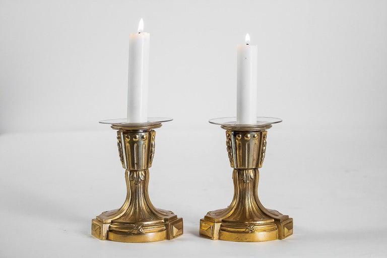 French Louis XVI period pair of small gilt bronze candlesticks, circa 1780  An elegant et decorative pair of small gilt bronze candlesticks also called