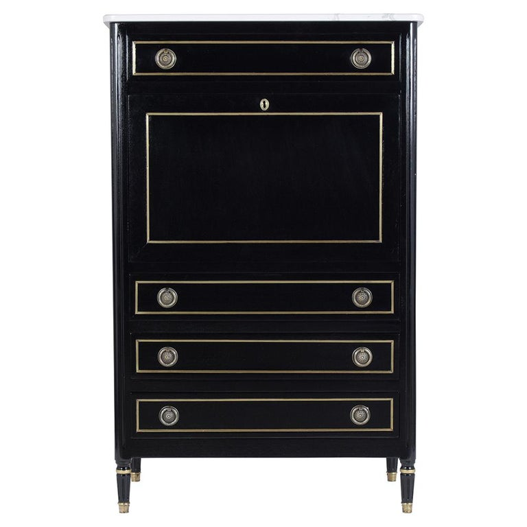 An elegant French Antique Louis XVI Secretary crafted from mahogany wood. This extraordinary piece features newly ebonized color with a lacquered finish and eye-catching brass molding accents details a new quartz white marble top a drop front desk