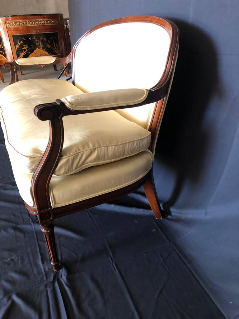 Beautiful Louis XVI style mahogany loveseat or settee with sumptuous high quality ivory silk and down seat cushion and upholstered arm rests. Silk has a few minor marks; see photos. Nicely carved details and tapered elegant legs. #2295.