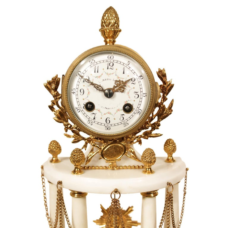 An elegant French 19th century Louis XVI style ormolu and white carrara marble signed clock. The clock is raised by chased ormolu supports below a demilune shaped base decorated with ormolu borders and a swaging floral garland. Above are four