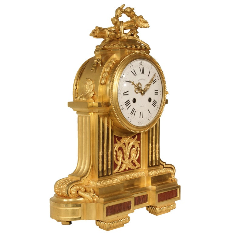 An impressive French mid-19th century Louis XVI style ormolu and Griotte de Campan Rouge marble clock signed 'Raingo Freres', Paris. The clock is raised by an impressive rectangular rounded base with marble inserts. The central support is finely