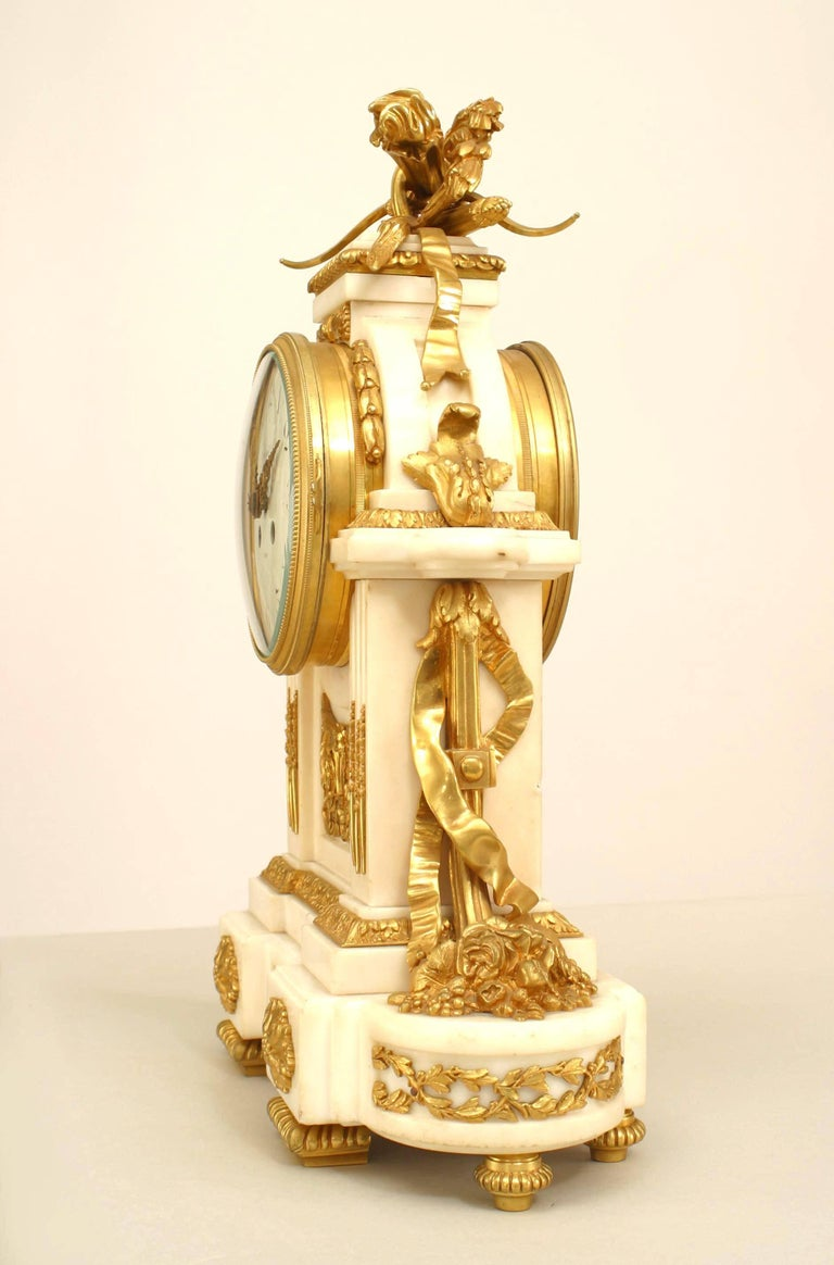 French Louis XVI style (19th century) white marble mantle clock with gilt bronze trim and a pediment with a wreath and arrows (clock face signed: HGER DU ROY, PARIS) (not working).