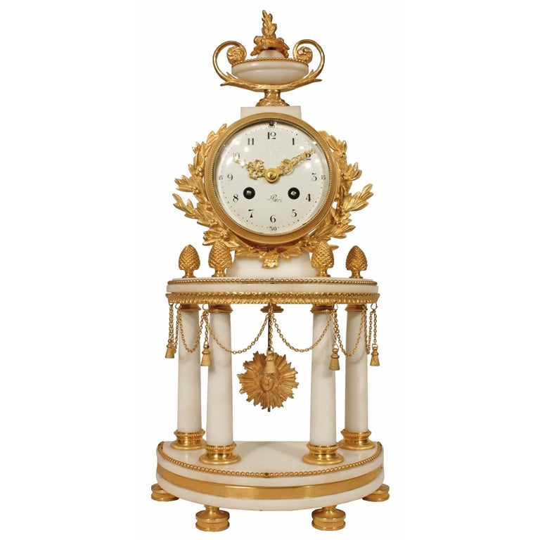 An impressive French 19th century Louis XVI style ormolu mounted on white Carrara marble clock Garniture set. The three piece set includes a pair of two arm candelabras ormolu mounted with beads and C scrolled arms. The clock is ornamented with