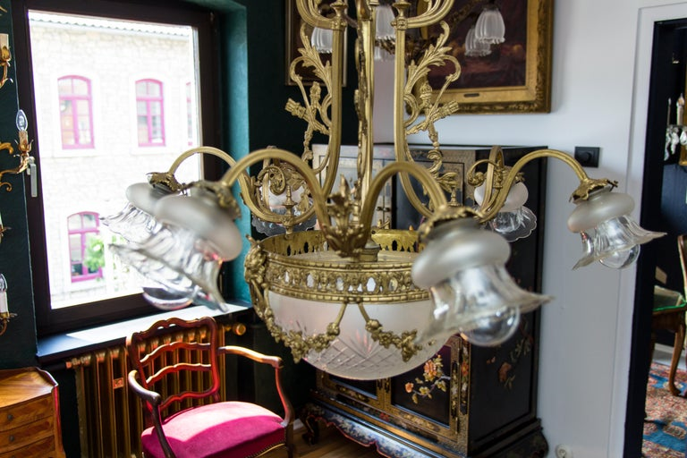 Louis XVI style bronze seven-light chandelier from 1920s. Six bronze arms, each with floral shape glass lamp shade, seventh light is located in the center of cut glass lampshade, decorated with bronze flower chains held by ram heads.