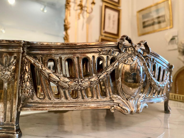 An elegant French 19th century Louis XVI style silvered bronze centerpiece with metal removable insert. The centerpiece is raised on columned feet and adorned in the neoclassical, Louis XVI vernacular, with swags, garlands and bows surrounding an