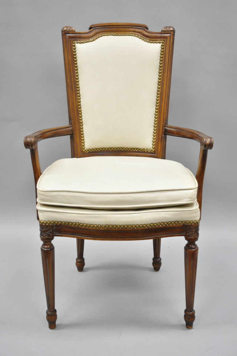 Set of eight French Louis XVI style walnut dining chairs with leather upholstery. Listing includes six side chairs, two armchairs, off white leather upholstery, nailhead trim, solid wood construction, tapered legs, and quality American