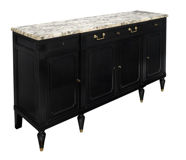 French Louis XVI style ebonized buffet made of solid mahogany and featuring an ebony French polish finish for a lustrous appearance. There are three dovetailed drawers above four doors that open to shelving. The tapered legs add elegance and the