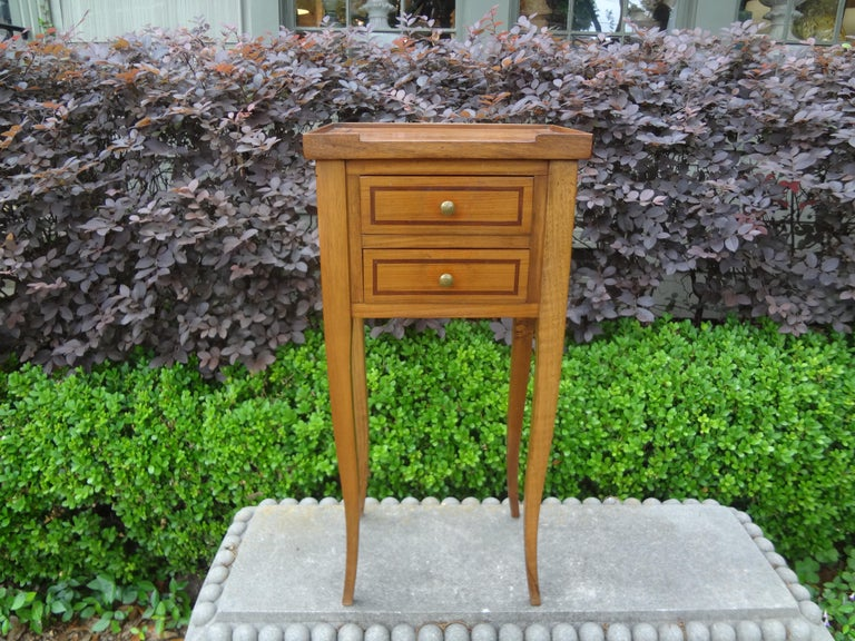 Stunning French Louis XVI style fruitwood side table or bedside table/nightstand. This charming French table has two drawers banded in a darker wood with bronze hardware and graceful legs.