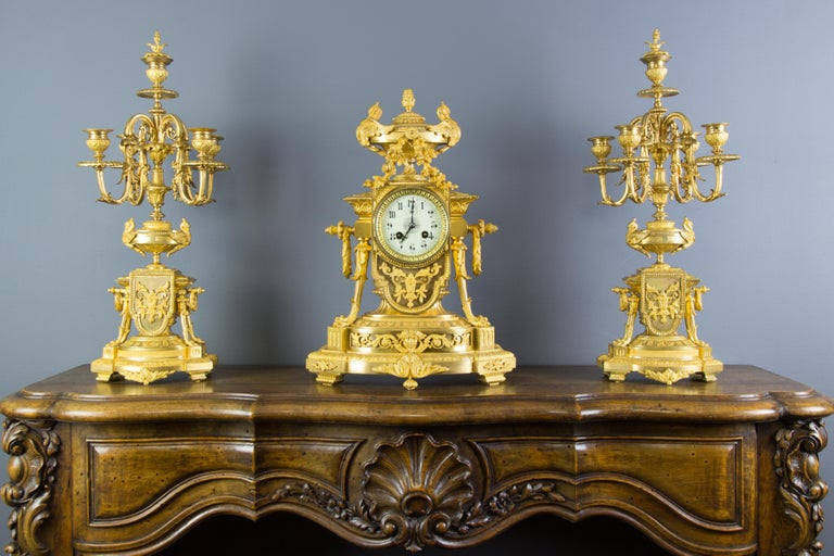 Stunning and very fine quality French late 19th century Louis XVI style gilt bronze mantel clock and a pair of five-light candelabra; the mantel clock of architectural form surmounted by urn finial, flanked by two swans. The mantel clock is centered