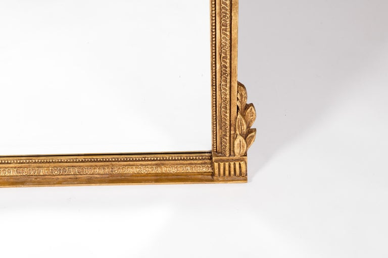 French Louis XVI style gilt wood beveled hanging wall mirror. The beveled hanging mirror is in excellent vintage condition. Minor wear consistent with use / age. The mirror measure about 46 inches high x 40 inches wide.