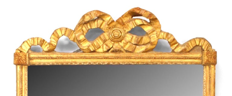 French Louis XVI style giltwood wall mirror with carved filigree ribbon design pediment with original glass and raised block corners and rosette details. (19th century).