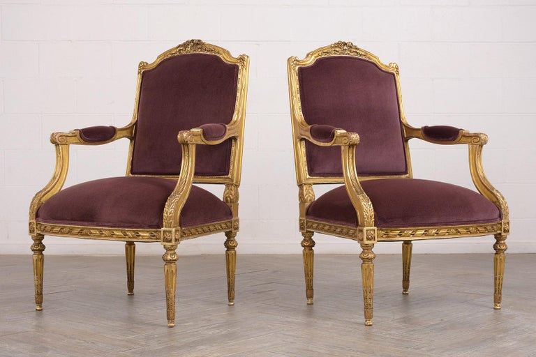 This pair of 1880s French Louis XVI-style armchairs have been completely restored. The giltwood frames feature the original finish and are adorned with intricately carved details of flowers, leaves, scrolls, and traditional motif decorative bands.