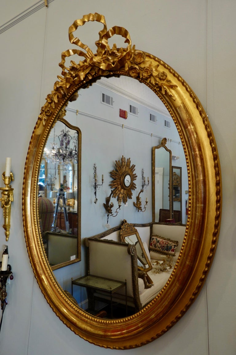 French Louis XVI style giltwood oval mirror with a large, finely-carved bow cartouche flanked by roses (circa 1830). The deeply molded frame features pearl beading on the interior perimeter and twisted molding on the exterior. Mercury glass and