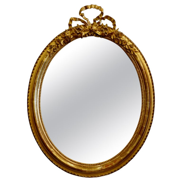 French Louis XVI Style Giltwood Mirror with Large Carved Bow Cartouche For Sale