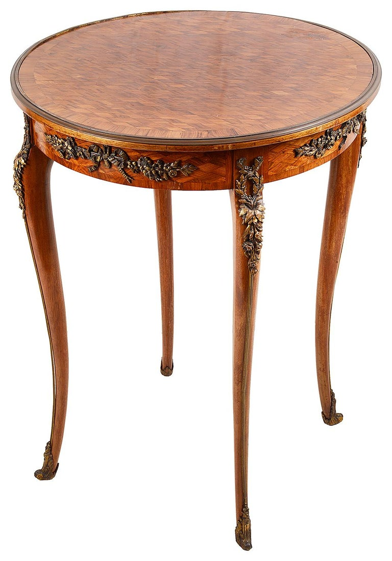A very good quality 19th century parquetry inlaid side table / Gueridon, having gilded ormolu moldings and foliate swag mounts, raised on elegant cabriole legs, terminating in scrolling ormolu feet. In the manner of 'Francoise Linke'. Measure: 59cm