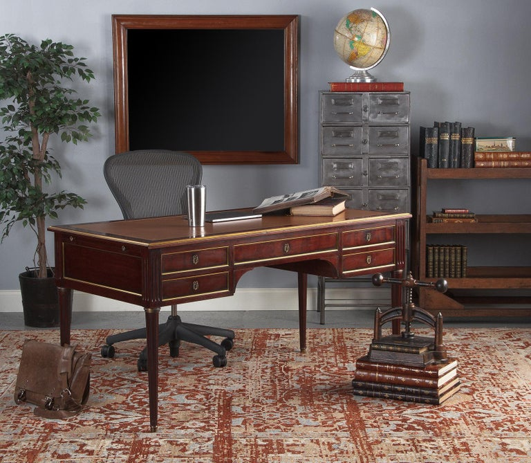 A handsome and useful Louis XVI style mahogany desk with leather top, French circa 1950. Dark red mahogany wood trimmed in brass detail and topped with a tobacco-tan colored writing top with gilt embossing. Square corner posts are fluted, with