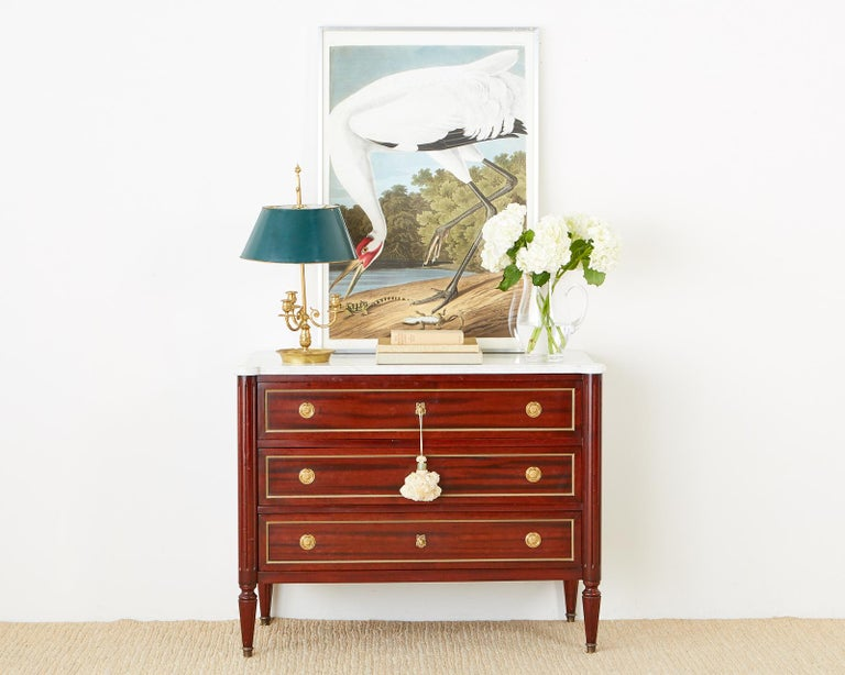 Fine French mahogany commode, chest of drawers, or dresser featuring a dramatic conforming Carrara marble top. The beautifully crafted case is fronted by three large storage drawers with bronze trim and brass pulls. Each side is pilastered with a
