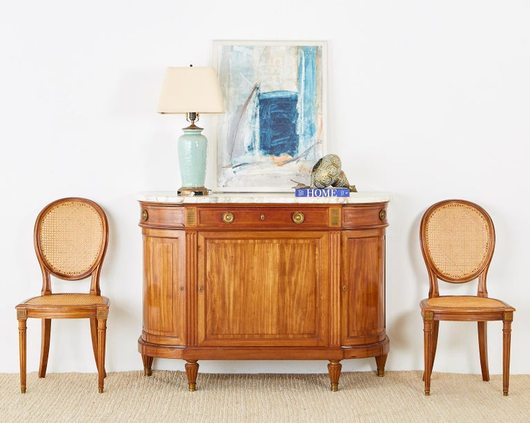 Distinctive French radiant mahogany sideboard server or buffet featuring a large Carrara marble top. Made in the Louis XVI or Directoire taste with neoclassical bronze mounted designs between the three top storage drawers. The case is crafted with