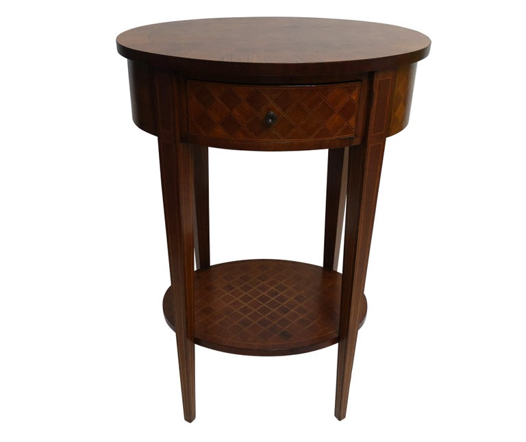 A Louis XVI style oval shape mahogany parquetry side table with satinwood and ebony inlay and a mahogany crossbanding border. Having a single drawer and a lower shelf.