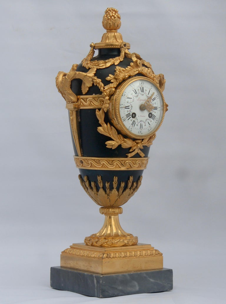 A French Louis XVI style ormolu and lacquered tole covered vase shape mantel clock Blue lacquered tole covered with ormolu chiseled garlands decorated with flowers and knotted flowers, acanthus and asparagus. At damping, a seeded bud, it rests on a