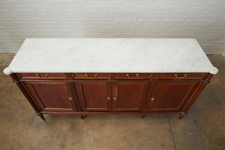 Distinctive French mahogany sideboard or buffet featuring a dramatic white Carrara marble top. Made in the grand Louis XVI Directoire style with fluted pilaster columns on each front corner. There are four storage drawers and four enfilade style