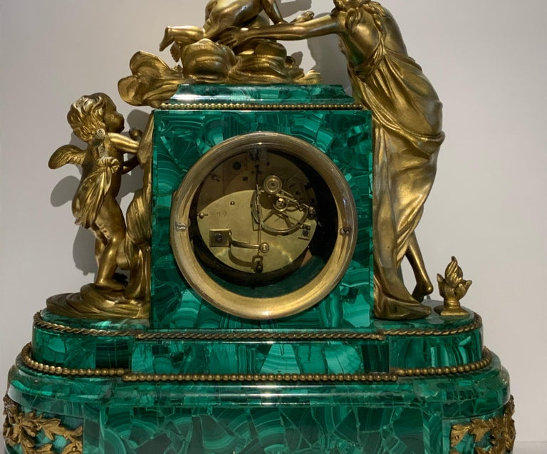 This mantel clock depicts a mythological group scene in bronze of figures representing a cupid with a torch in his right hand in clouds made of scrolls and foliage flirting with a semi nude Venus while another cupid is observing them. The clock case