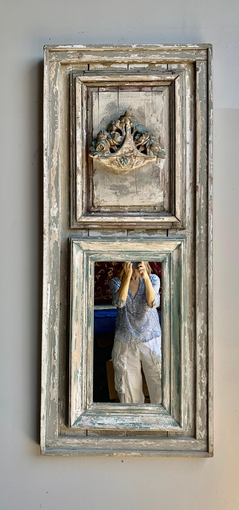Early 20th century carved wood painted trumeau with a center carved basquet of flowers at the top of the mirror. Beautiful worn paint throughout. Great scale for smaller entry or powder room.