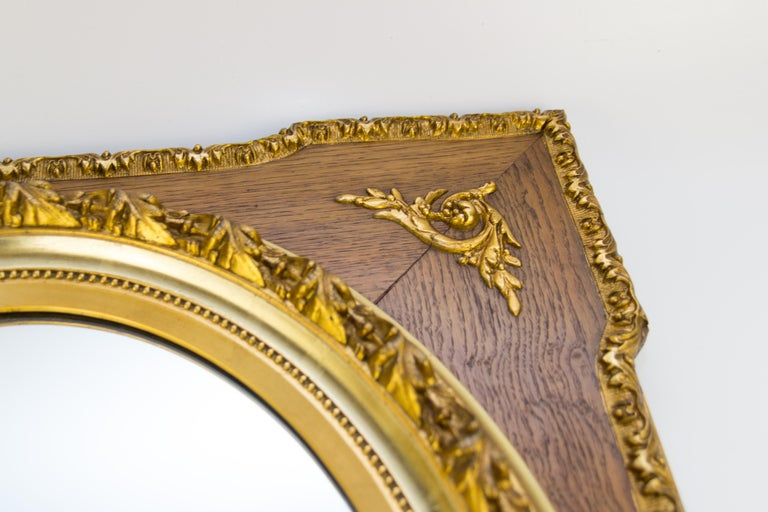 A French Louis XVI style rectangular massive oak frame with central oval mirror plate, surrounded with a parcel-gilt garland molding, decorated with gold-colored acanthus leaves ornaments, made of composition material. From the 1920s. Dimensions: