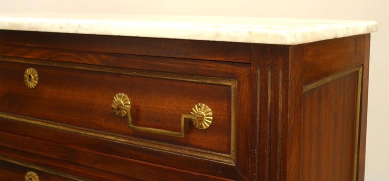 French Louis XVI style (19th/20th century) mahogany semanier (seven drawer chest of drawers) with bronze doré handles and trim supported on fluted tapered legs with a white marble top.