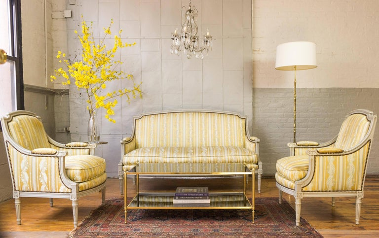 Louis XVI styled sofa with grey patina carved wooden frame upholstered in a striped silk fabric. The fabric is striped in white, yellow and blue with a floral design. This sofa has decorative nailheads and a loose down cushion seat.