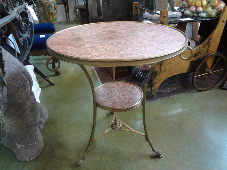 Stunning French Louis XVI style two tier bronze dore and marble gueridon. This beautiful antique French Louis XVI style side table or center table has an unusual variegated rouge marble top within an ormolu border. This versatile two tiered table