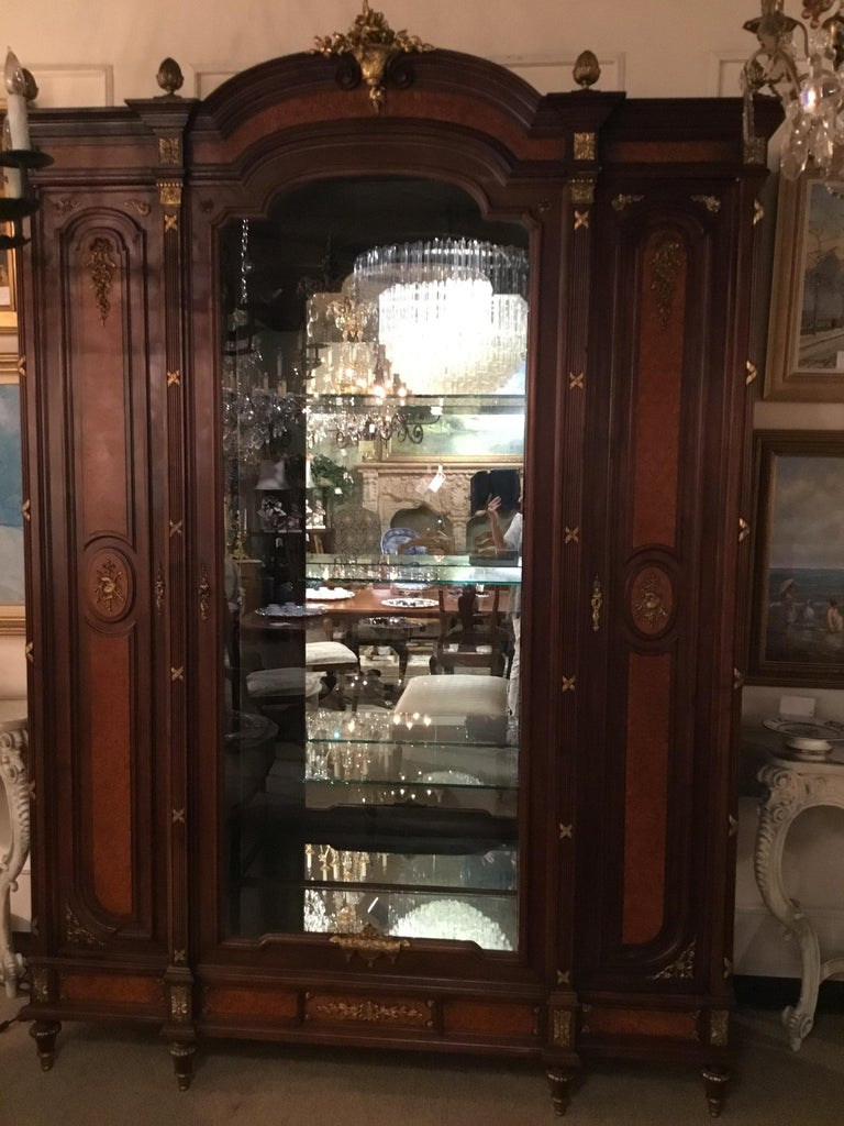 Exceptional display cabinet with center opening door to fitted interior with three glass shelves that are moveable, 19th century. It has a mirror back and mirror on the bottom. Two doors open on each Side for storage that are fitted with four