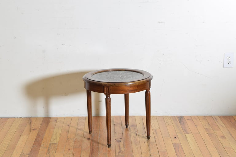 The circular top with a raised edge and inset marble top, the apron with fluting and raised on circular fluted legs ending in brass casters.