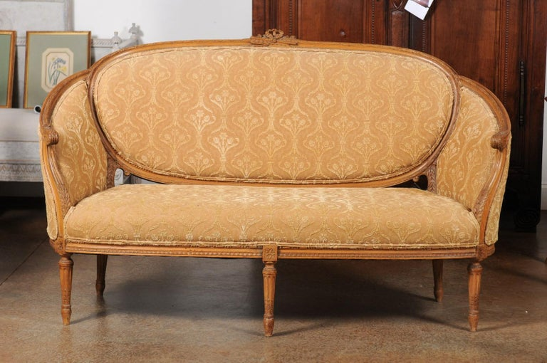 A French Louis XVI style 'canapé en corbeille' from the 19th century, with carved crest, fluted legs and upholstery. Created in France during the 19th century, this canapé features a wraparound back accented with ribbon-tied foliage and flute. The