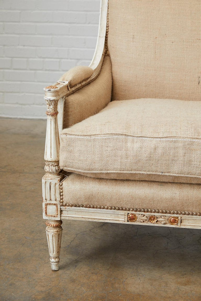 Stunning French painted settee or loveseat made in the Louis XVI Gustavian taste. Features a beautifully carved frame with neoclassical acanthus motifs. Each side has Directoire style column arm supports with a gilt rosette on the top. The flat
