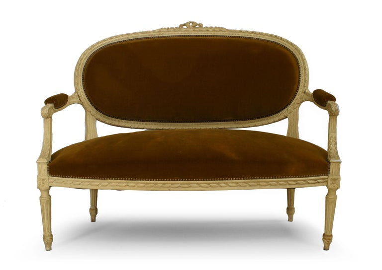 French Louis XVI style cream painted loveseat with bow knot carved back crest and velvet upholstered seat and back.