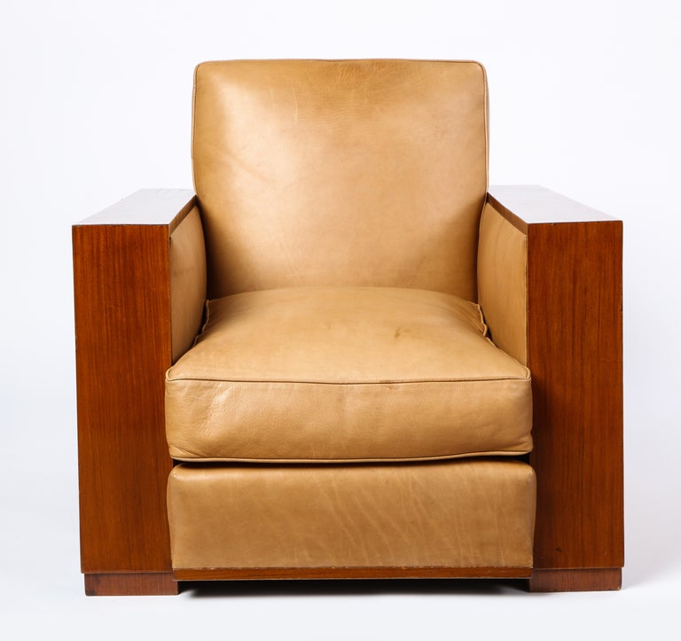 This French mid-20th century leather upholstered and mahogany club chair is attributed to Dominique. Upholstered with a soft and comfortable buttery tan leather over warm mahogany. It's art deco style design is practical and chic and would be a