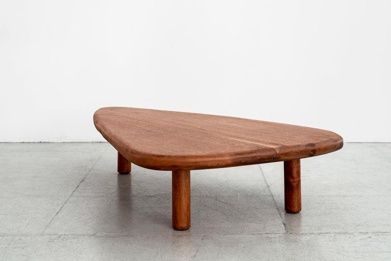 French 1950s freeform coffee table in mahogany wood. Wonderful guitar pick shape with 3 cylinder legs and radius corners. Great patina to wood.