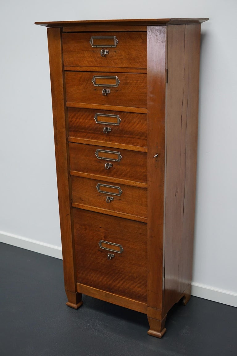 This vintage mahogany bank of drawers dates from the 1930s and was made in France. It features a mahogany frame, drawers with mahogany fronts and metal handles. The drawers can be locked. A small piece of the left back leg is missing.