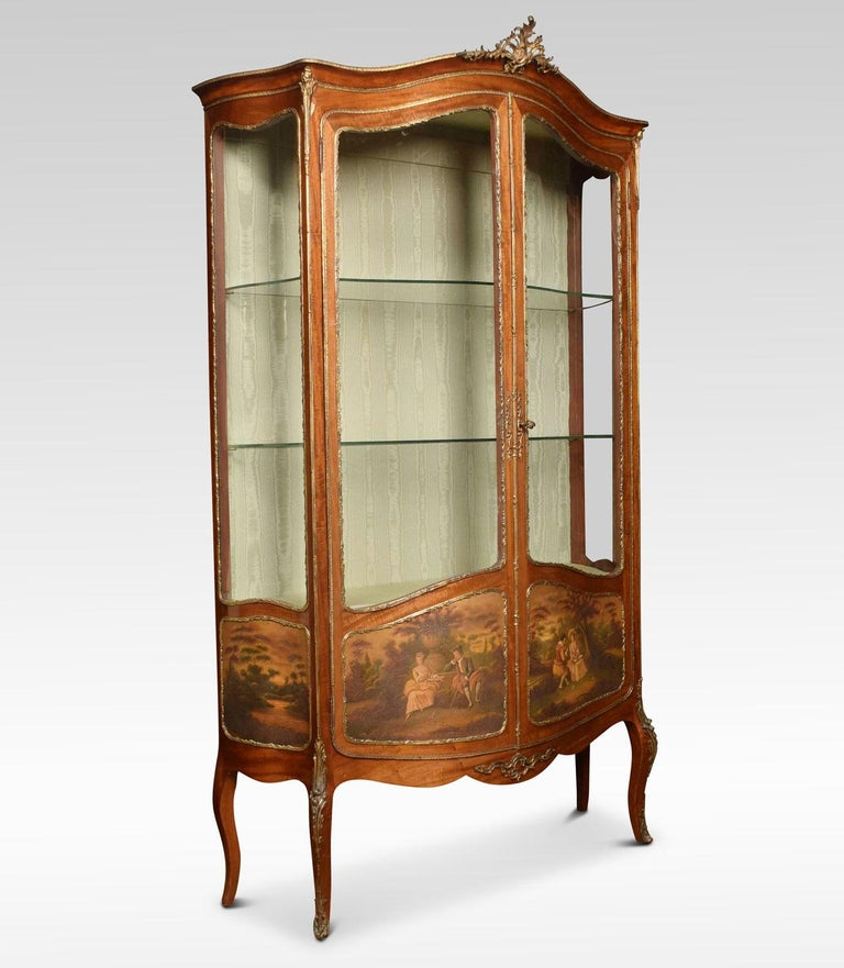French mahogany, gilt metal Vernis Martin vitrine. The flared serpentine top with pierced Rococo motif. Over a pair of serpentine glazed doors and sides, enclosing upholstered silk interior with two glass shelves. The lower doors and sides with
