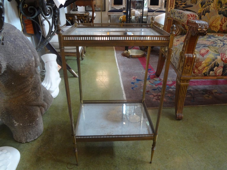 Stunning French Louis XVI style bronze two-tiered table or gueridon. This gorgeous side or end table has beautifully distressed reverse decorated/églomisé mirrored tops with pierced galleries with elegant thin legs. This bronze/brass table is