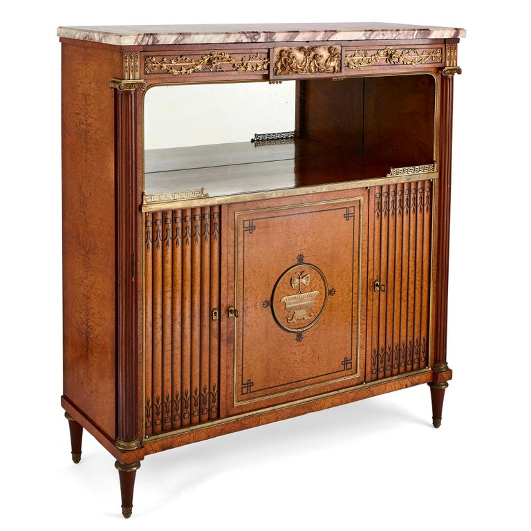 This wonderful side cabinet was created in France in the 19th century. The cabinet is crafted from amboyna burl wood, with inlaid ebony wood decoration and gilt bronze (ormolu) mounts.  The cabinet is covered by veined white marble. This tops a
