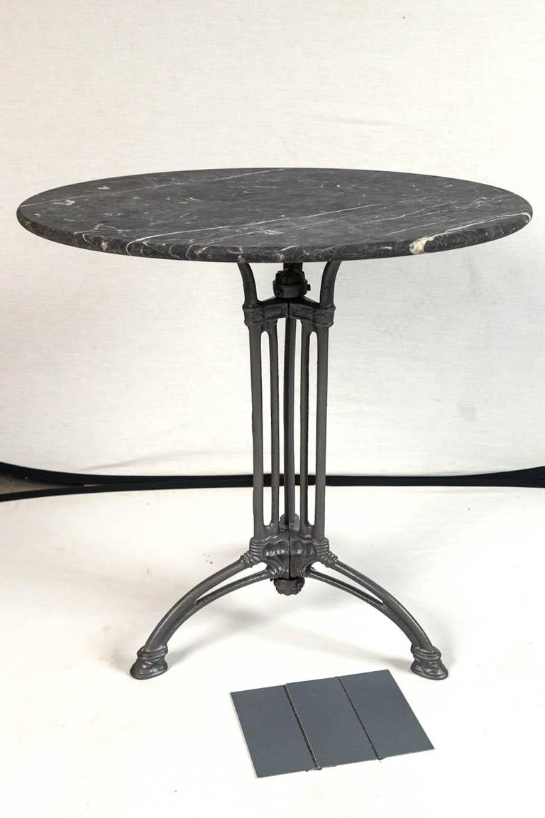 French marble top cast iron Bistro table, circa 1900. Original gray marble top with white veining. The tripod iron base has detailed cast designs in the Art Nouveau style.