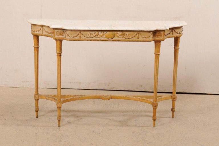 A French carved-wood console table with marble top from the mid 20th century. This vintage table from France has been designed with Neoclassical influences, and features a marble top which rests upon an apron carved with stringing garlands and an