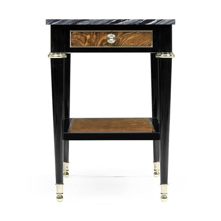 A French Louis XVI style, modernized, black lacquered and amber ash burl paneled side table with a rare variegated grey marble top, single drawer with brass pulls and capitals, a lower shelf stretcher and turned and tapered pegs raised on ball foot