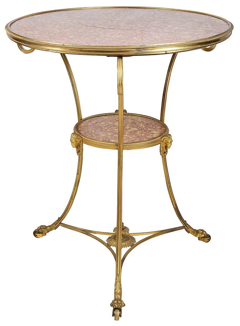 A very elegant late 19th century French gilded ormolu Gueridon, having a wonderful inset Rosa marble top, three scrolling out swept supports, an under tier also with a matching inset marble, Rams head and wreath mounts, terminating in classical claw