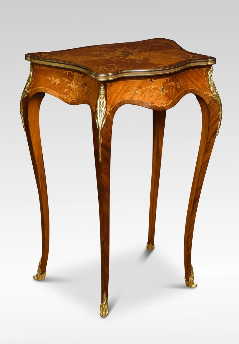 French marquetry dressing table with shaped lift up top inlaid with floral marquetry, and enclosed in brass rim. The top opening to reveal the upholstered interior. All raise upon four slender cabriole supports. Dimensions: Height 30 inches Width
