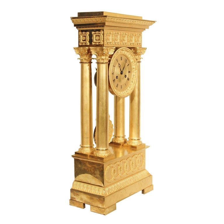 An exquisite French mid-19th century Empire style ormolu portico clock. The clock raised on a rectangular base with finely chased borders and satin and burnish finish interlocking circles. Above are four ormolu columns with berried laurel plinths