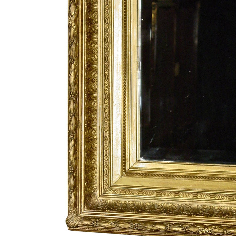 A French mid-19th century giltwood Louis XVI style mirror. The rectangular original mirror plate is framed within a carved frame with a laurel garland fluted border amidst acanthus leaves and twisted ribbon. This mirror may be displayed horizontally